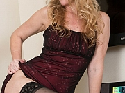 Long-legged milf blonde poses in black stockings