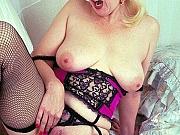 Busty amateur mom in black stockings poses on bed